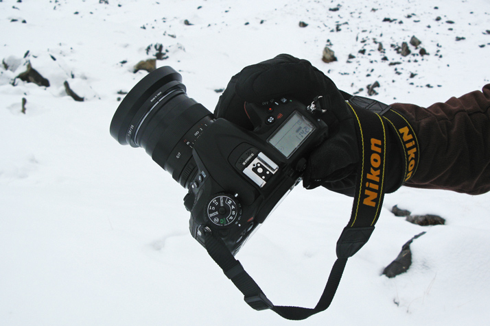 Photographer holding the Nikon D7200 with mountaineering gloves in the snow