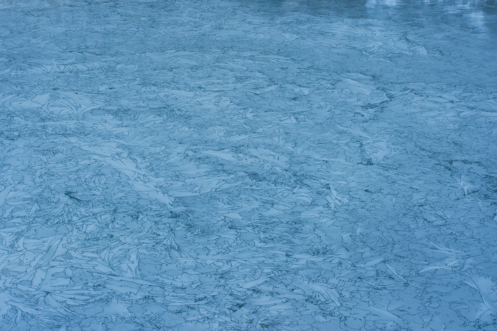 View of a miriad of Ice cracks forming geometric patterns in a frozen lake in the French Alps