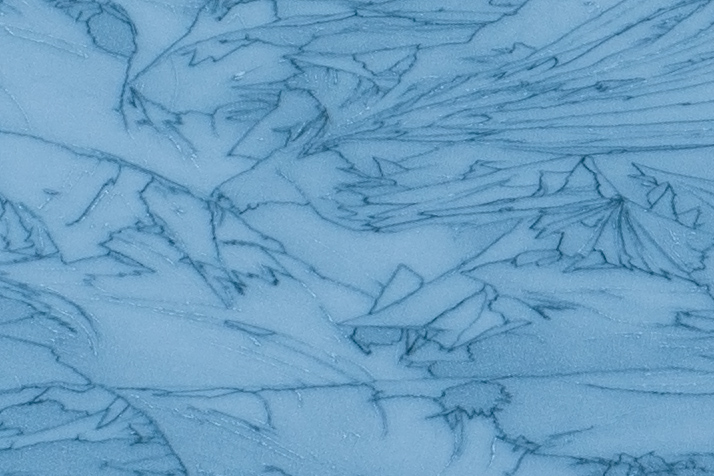 Nikon D7200 100 ISO test from a 100% crop of an image showing ice cracks forming patterns in a frozen lake in the French Alps