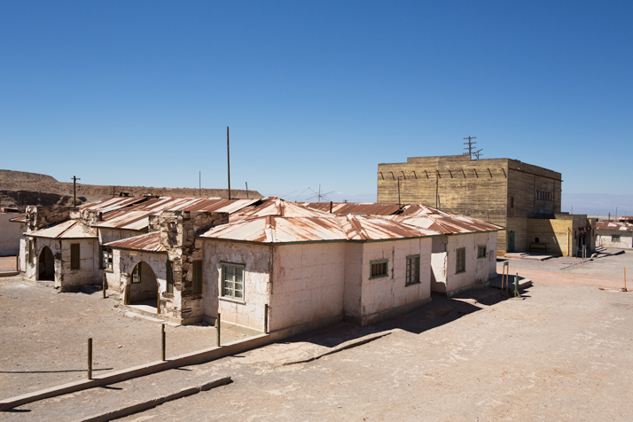 The small hospital in the foreground and the theatre in the background in the the ghost town Humberstone in Chile