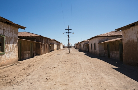 Road with a pole and the abandoned houses of the bachelor workers in Humberstone